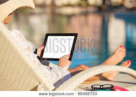 Woman using tablet computer by the pool