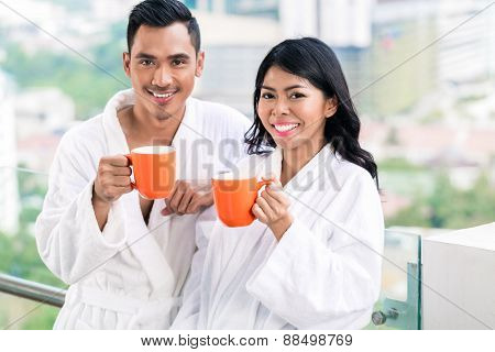 Asian couple in morning front of city skyline drinking coffee still in bathrobe