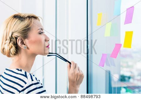 Chinese business woman planning and organizing with adhesive stickers