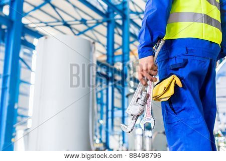 Industrial worker in factory with tools going to machine maintenance