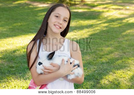 Cute Smiling Teen Girl Holding White And Black Baby Rabbit