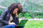 picture of saddening  - exotic beautiful young worried girl with dark curly hair using laptop in the garden - JPG