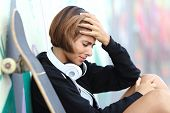 pic of depressed teen  - Worried or depressed teenager girl leaning on a wall with blurred graffiti - JPG