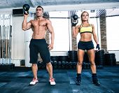 picture of kettles  - Muscular man and fit woman workout with kettle ball at gym - JPG