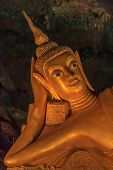 pic of cave  - Head of the golden statue of Reclining Buddha in buddhist cave temple in Wat Tham Suwankhuha cave  - JPG