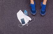 picture of bottle water  - Top view of man legs with sneakers - JPG