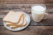 picture of whole-grain  - whole grain bread and milk wooden background. [[** Note: Shallow depth of field ** Note: Visible grain at 100%, best at smaller sizes - JPG