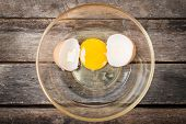 stock photo of yolk  - Cracked chicken egg with yolk and egg shell on dish wooden background - JPG