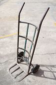 image of hand-barrow  - Empty metal old hand truck on cement floor - JPG