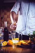 foto of sangria  - The man squeezes orange juice in a decanter for the preparation of sangria for home party - JPG
