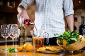 stock photo of sangria  - Man pouring red wine into a carafe - JPG