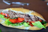 foto of baguette  - Healthy Tuna Baguette With Lettuce,Tomato,Cucumber On The Brown Plate On The Table ** Note: Soft Focus at 100%, best at smaller sizes - JPG