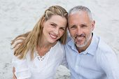 stock photo of couple sitting beach  - Happy couple sitting on the sand and looking at the camera at the beach - JPG