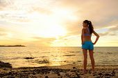 Aspirations - woman looking away with inspiration. Fitness woman after run in sunset on beach lookin poster