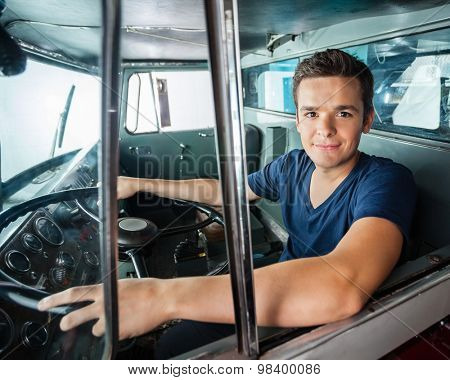 Portrait of confident male firefighter driving firetruck
