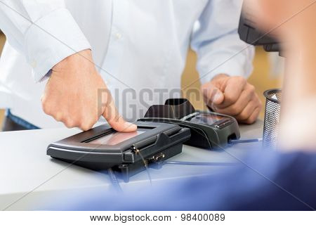 Midsection of customer giving thumb impression to make payment in pharmacy