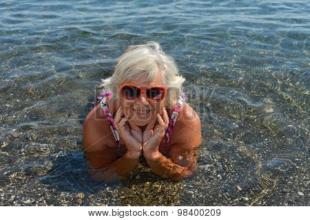 Aged Lady Is Lying In Water Shallow Of Sea Beach.