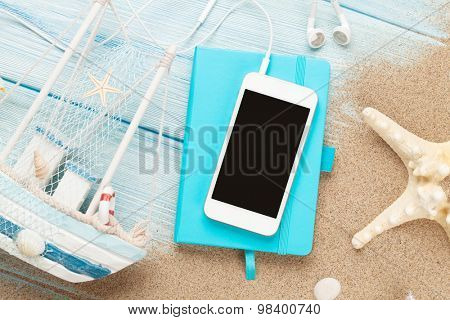 Smartphone and notepad on sea sand with starfish and toy boat. Top view with copy space