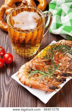 Grilled shrimps, pretzel and beer mug on wooden table