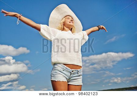 Happy girl with outstretched arms against cloudy sky