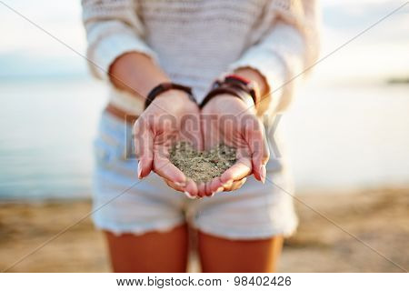Close-up of girl holding sand on her palms