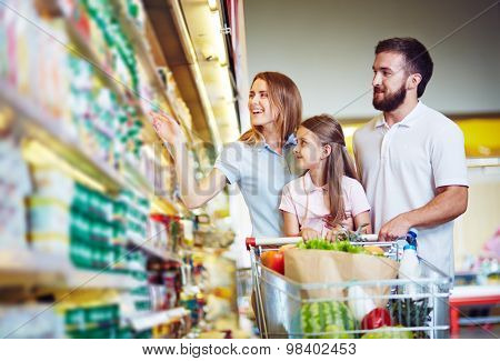 Young family in hypermarket choosing products