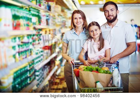 Modern family looking at camera while buying food in supermarket