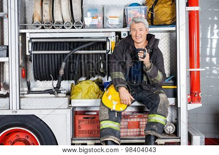 Portrait of happy fireman holding coffee mug while sitting in truck at fire station