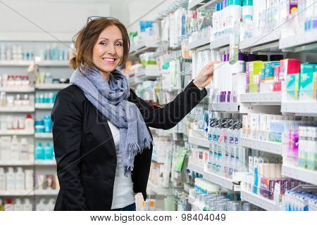 Portrait of smiling female consumer choosing product in pharmacy