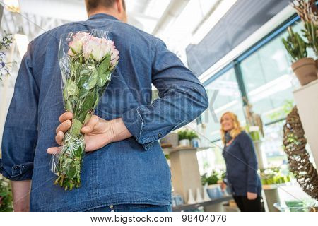 Rear view of man hides bouquet of roses from woman in flower shop