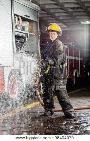 Portrait of confident young firewoman spraying water during practice at fire station