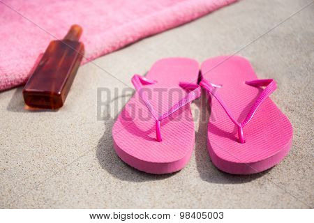 Summer Concept - Flip Flops, Towel And Suntan Lotion Bottle On Sandy Beach