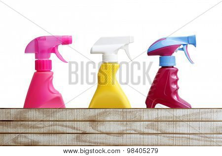 Three cleaning bottles above wood