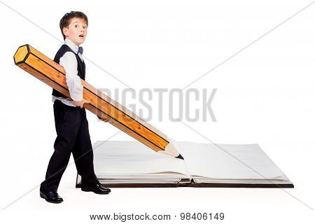 A boy writes with a big pencil in a big book. Educational concept. Isolated over white.