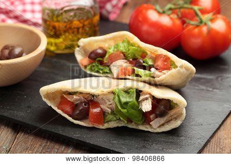 Pita bread stuffed with turkey meat, tomato, kalamata olives, and lettuce