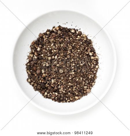 Peppercorns in white dish, isolated.  Overhead view.