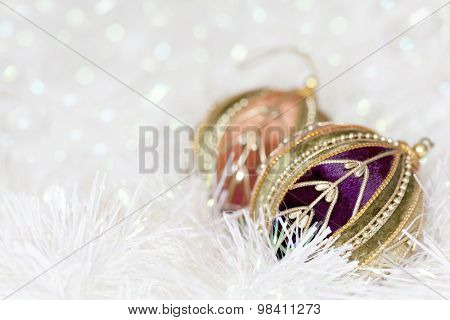 Christmas baubles in white tinsel, with blurred background.