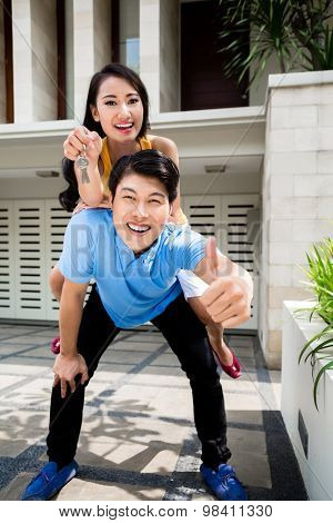 Chinese woman and man enjoying the new home they bought giving the thumbs up