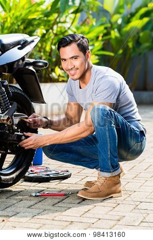 Asian man working on his motor scooter looking at camera