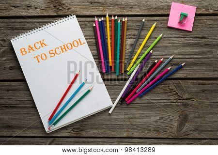 Back to School pupils art pencils and pad on wooden desk from above