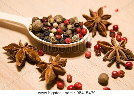 Spoon Filled With A Mixture Of Grains Of Pepper And Star Anise On A Wooden Surface