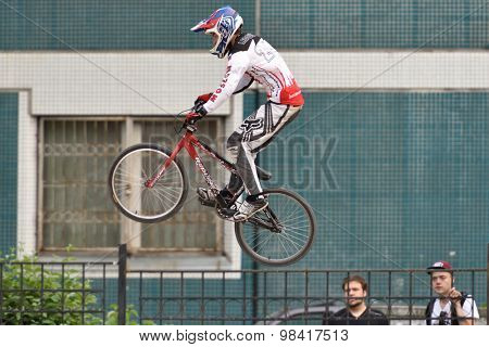 ST. PETERSBURG, RUSSIA - AUGUST 6, 2015: Spectators watch the unidentified biker in the BMX race Cruiser. The competitions is a stage of the BMX racing championship of Russia