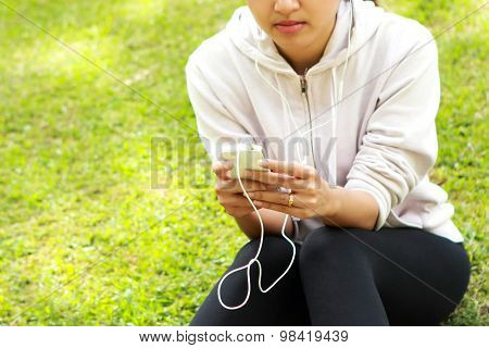 A Woman Sitting While Listening A Music Using Earphone From Mobilephone