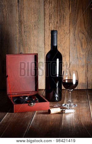Bottle And Glass Of Red Wine On Wooden Table.