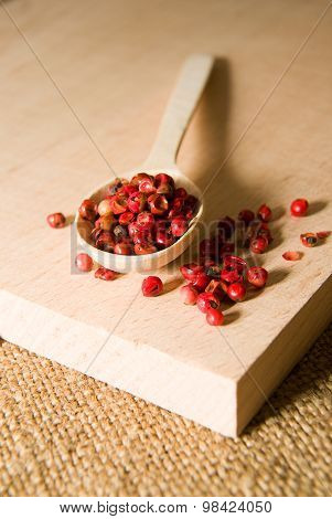 Spoon Filled With  Of Grains Of Pepper On A Wooden Surface