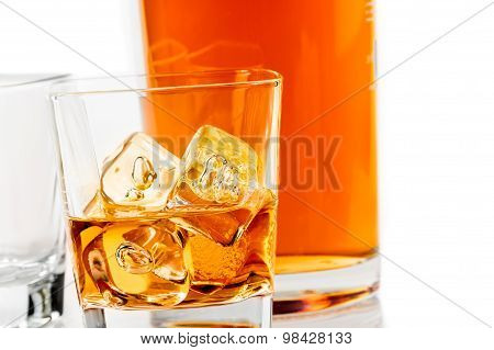 Two Glasses Of Whiskey Near Bottle On White Background With Reflection
