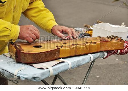 Old man is playing on zither