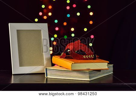 Still Life With Mask On Book And Picture Frame On  Wooden Table In Bokeh Background