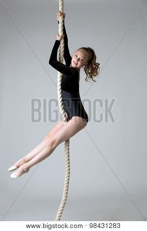 Charming little power gymnast climbs on rope
