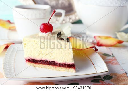 Tasty piece of cheesecake on plate on table close up